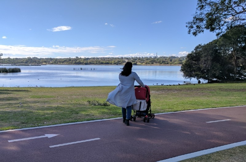 Image of lady walking with a pram by the water at Picnic Cove Park in Joondalup